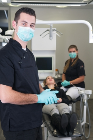 Dentist in the front, nurse and patient in the background photo