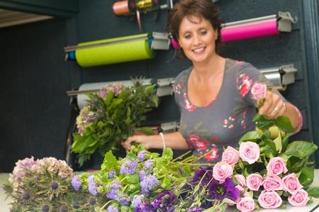 Женский флорист работает в магазине цветов, что делает букет готов к клиенту
