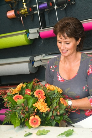 Female florist working in a flower store, making the bouquet ready for the customer Stock Photo - 12942806