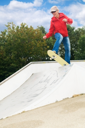 crazy hair: Cool granny on a skateboard at a skatepark Stock Photo