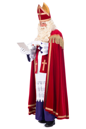 studioshoot: Modern Santa Claus using a tablet instead of his book Stock Photo