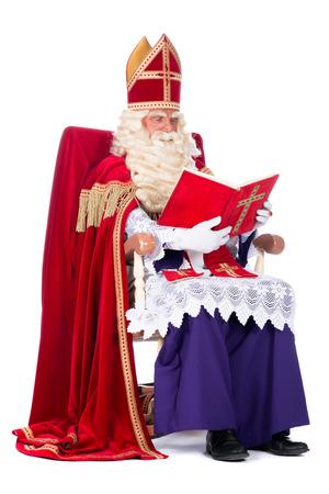 Санта-Клаус отдыхает на стуле, читая в книге Фото со стока