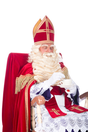 Sinterklaas is resting on his chair, drinking a cup of coffee photo