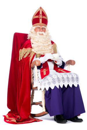 studioshoot: Santa Claus is resting on his chair, drinking a cup of coffee