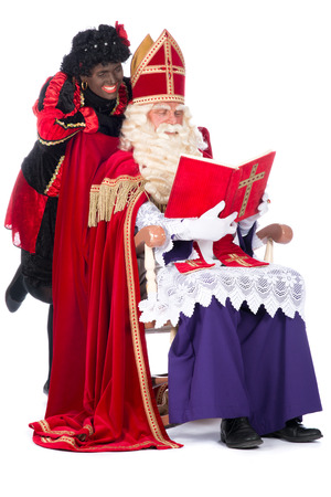 zwarte piet: Sinterklaas is reading in his book while Zwarte Piet is with him
