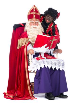 studioshoot: Sinterklaas is reading in his book while Zwarte Piet is with him