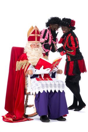 zwarte piet: Sinterklaas is reading in his book while Zwarte Piet is with him