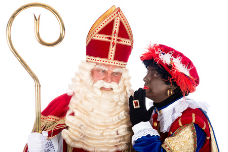 Zwarte Piet is whispering something in the ear of Sinterklaas