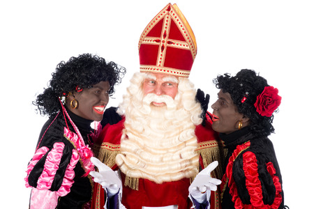Zwarte Piet is whispering something in the ear of Sinterklaas photo