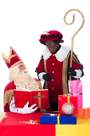 black pete: Sinterklaas is reading in his book while Zwarte Piet is with him