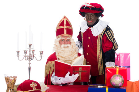 Sinterklaas is reading in his book while Zwarte Piet is with him