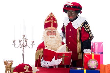 Sinterklaas leest in zijn boek, terwijl Zwarte Piet is met hem Stockfoto