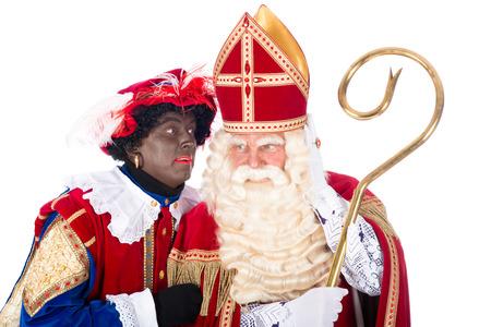 Zwarte Piet is whispering something in the ear of Sinterklaas photo