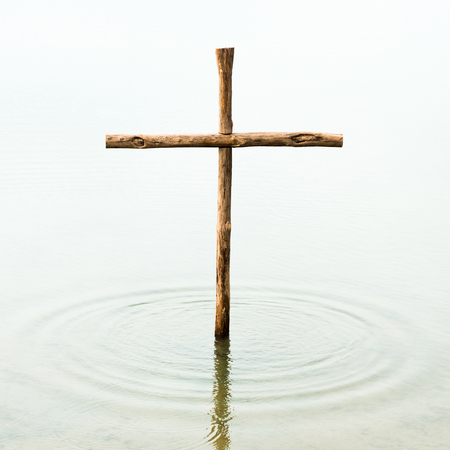 The cross is standing in the water, symbol for washing off our sins by Jesus, who died on the cross for all people