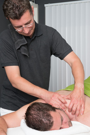 Massage therapist is working with a client Фото со стока