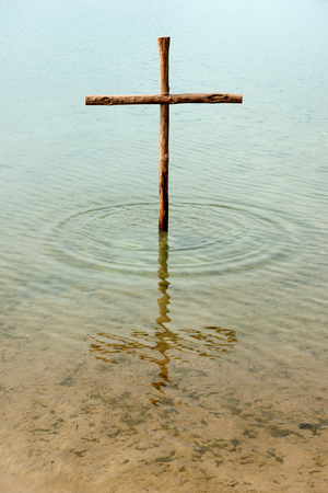 sins: The cross is standing in the water, symbol for washing off our sins by Jesus, who died on the cross for all people