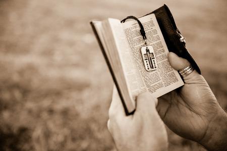 Man reading a bible outside