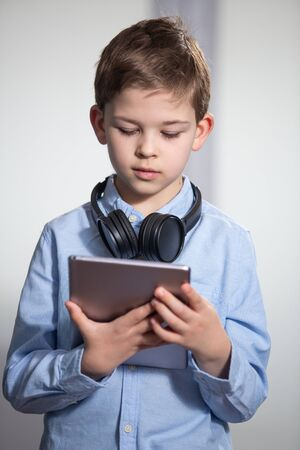 a lovely young pupil looking at his tablet with headphones Banco de Imagens