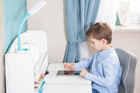 learn form home - lovely small boy in blue shirt sitting at the desk using his tablet Reklamní fotografie