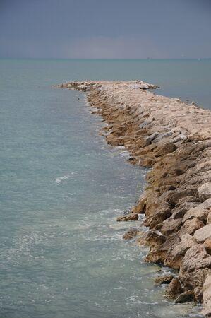 Breakwater of rocks in the sea Malaga, Andalucia