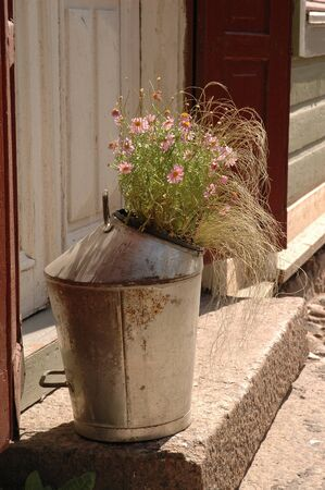 Metal bucket with flowers at the entrance to the house in Porvoo village Finland