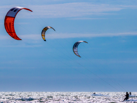 surfen: three kite surfers on the sea
