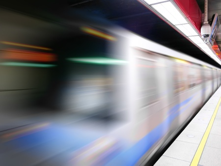 Moving train in subway station photo