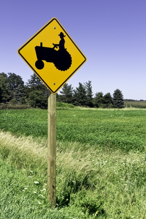 tractor warning sign: Farm tractor road sign against blue sky