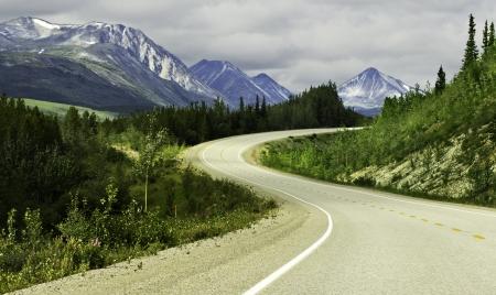 Gebogen asfaltweg in de hoge bergen van Alaska