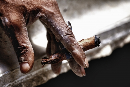 havana cigar: Old hand keeping smoldering cigar Stock Photo