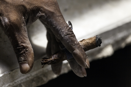 havana cigar: Old man hand keeping smoldering cigar Stock Photo
