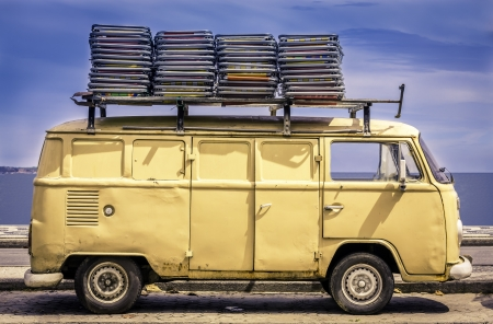 60s hippie: Vintage van in the beach of Ipanema with chairs on the roof Stock Photo