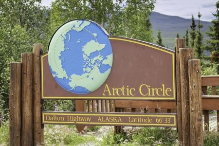 Arctic Circle sign on Dalton Highway in Alaska photo