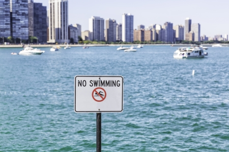 No swimming sign against tall buildings photo