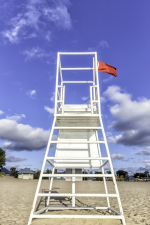 Water lifeguard stand with red flag photo