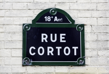 Traditional Paris plaque with street name on white brick wall photo