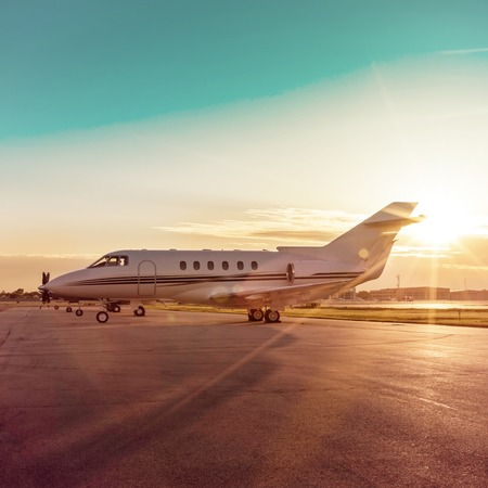 Business plane at airport during sunset Stock Photo
