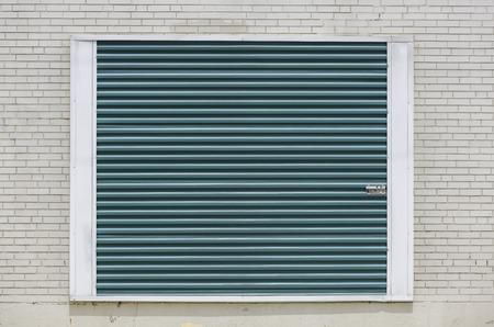 Green storage unit door on white brick wall photo
