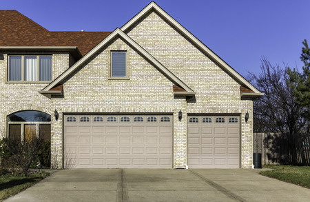 Traditional three car wooden garage with driveway