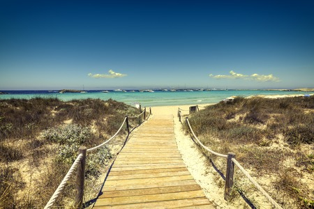 Entrance to the beach with wooden walkway in tropical island photo