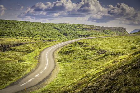 Curved asphalt road in high mountains of Iceland photo