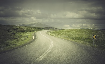 Curved shape asphalt road in high mountains of Iceland photo