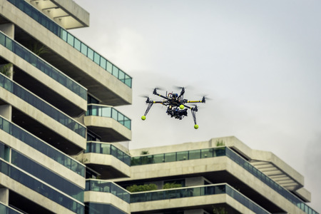 turning operation: Professional drone with camera flying above residential area