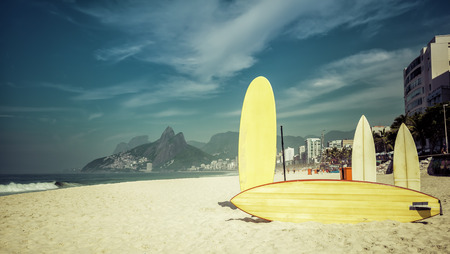 Surfboards standing upright in bright sun on the beach at Ipanema, Rio de Janeiro Brazil