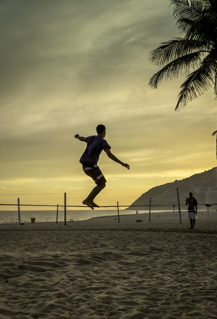 slack: Man practices slack lining at Ipanema Beach in Rio de Janeiro during sunse Stock Photo