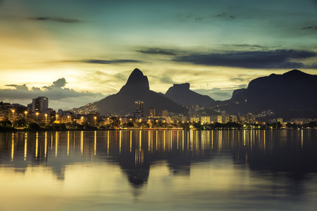 Sunset behind mountains in Rio de Janeiro with water reflection, Brazil