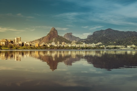 janeiro: Sunrise over mountains in Rio de Janeiro with water reflection and light leak, Brazil