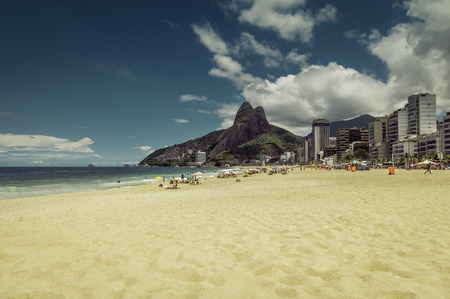 Bright sun on Ipanema Beach with people relaxing against Rio de Janeiro skyline in Brazil.