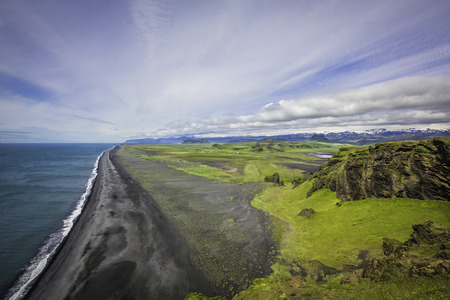 most popular: The black sand beach with typical Icelandic mountain landscapes aerial view