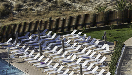 Empty sunbeds by the pool and the beach